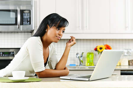 using computer: Thoughtful black woman using computer in modern kitchen interior