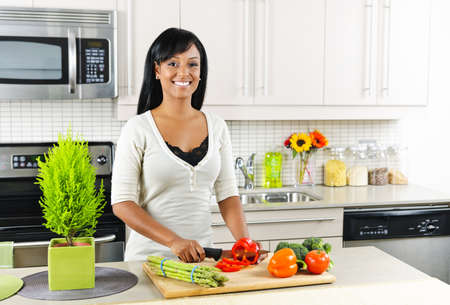 cutting: Smiling black woman cutting vegetables in modern kitchen interior