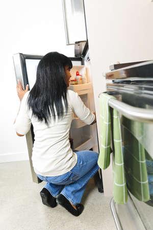 fridge: Black woman looking in fridge of modern kitchen interior