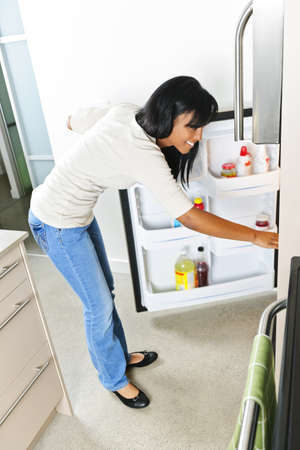 Black woman looking in fridge of modern kitchen interior photo