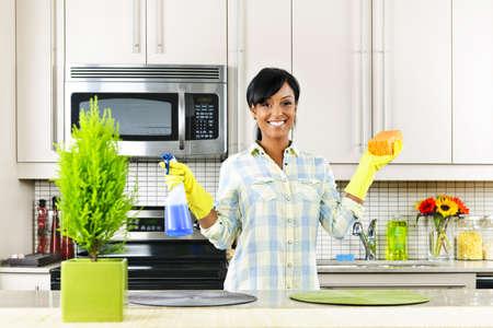 d�sinfectant: Souriante jeune femme noire avec une �ponge et de caoutchouc gants de cuisine nettoyage
