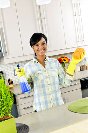 working woman: Smiling young black woman with sponge and rubber gloves cleaning kitchen