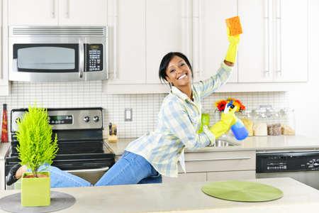 desinfectante: Sonriente joven negra bailar y disfrutar de limpieza de la cocina Foto de archivo