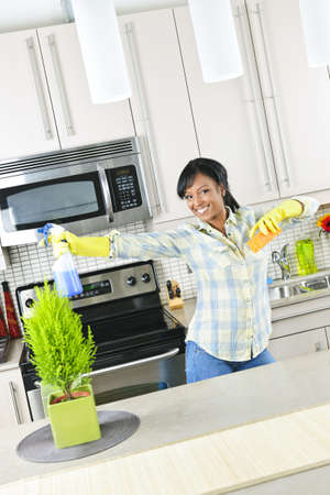 Smiling young black woman dancing and enjoying cleaning kitchen 版權商用圖片 - 8878879