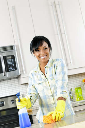 Smiling young black woman with sponge and rubber gloves cleaning kitchen photo