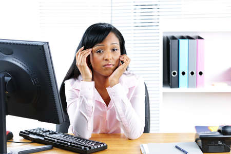 bothered: Unhappy young black business woman at desk in office Stock Photo