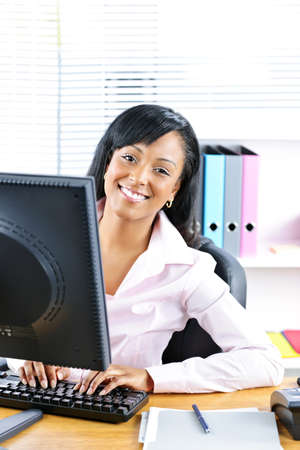 Young smiling black business woman at desk typing on computer Stock Photo - 8871772