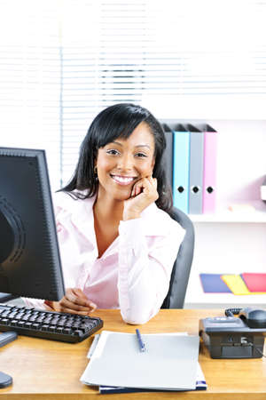 Smiling young black business woman at desk in office photo