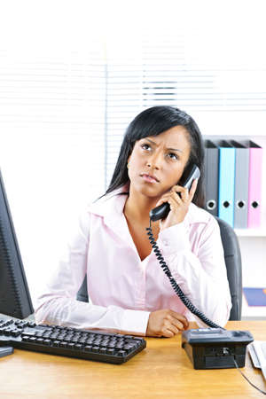 Concerned young black business woman on phone at desk in office photo