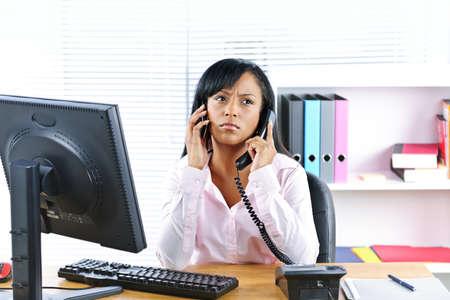 femme inqui�te: Jeune femme d'affaires noire multit?che ? l'aide de deux t?l?phones dans le bureau