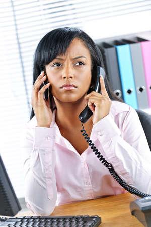 phone handset: Giovane donna di affari nero multitasking utilizzando due telefoni in ufficio