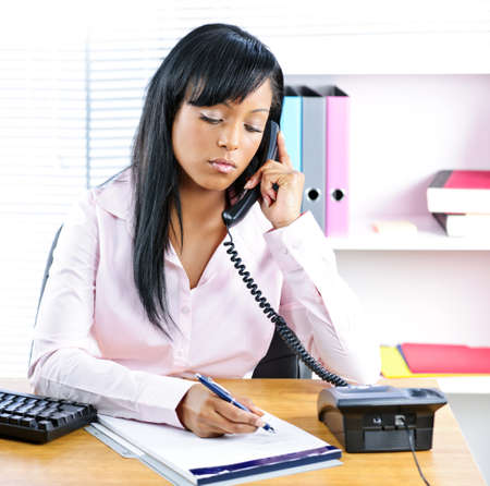 important phone call: Serious young black business woman on phone taking notes in office