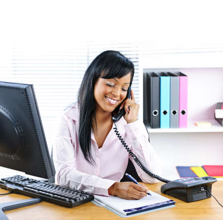 business woman: Smiling young black business woman on phone taking notes in office