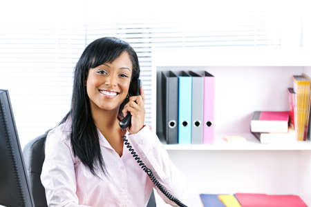 service desk: Smiling young black business woman on phone at desk in office Stock Photo