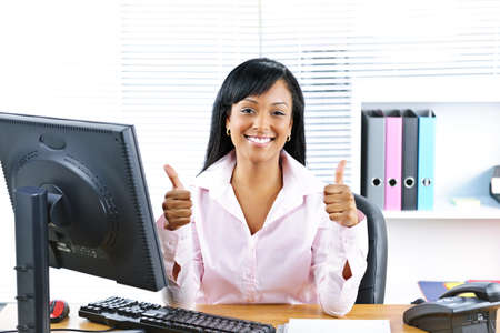 Smiling black business woman giving thumbs up gesture at desk in office Stock Photo