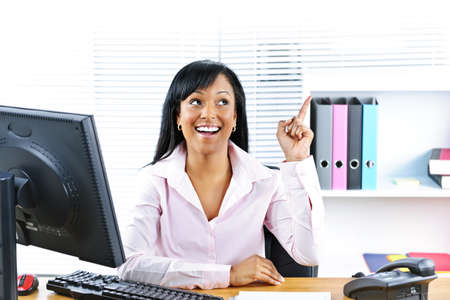 Smiling black business woman pointing up with idea at desk in office photo