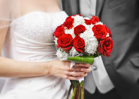 Bride and groom holding bridal bouquet close up photo