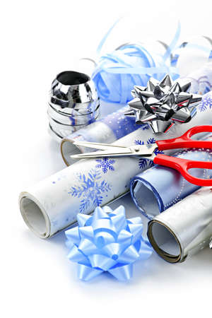 scissors: Rolls of Christmas wrapping paper with ribbons, bows and scissors