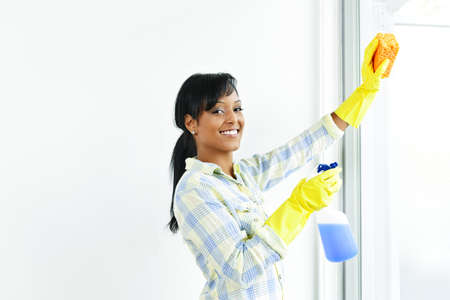 Smiling black woman cleaning windows with glass cleaner photo