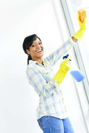 mujer limpiando: Sonriendo windows limpieza mujer negra con vidrio limpiador