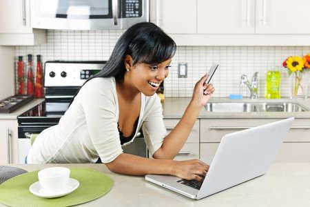 Lachende zwarte vrouw online winkelen met behulp van computer en credit card in keuken