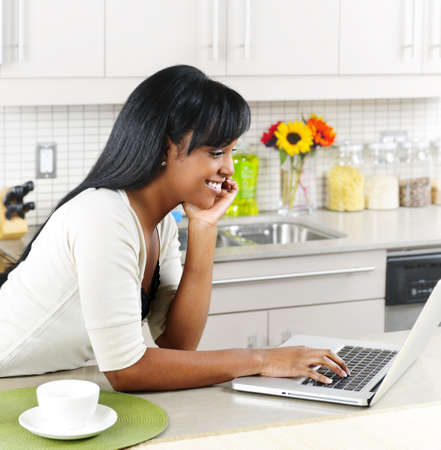 Smiling black woman using computer in modern kitchen interior Stock Photo - 8967354