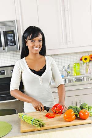 현대 부엌 인테리어에 웃는 흑인 여성 절단 야채 스톡 콘텐츠
