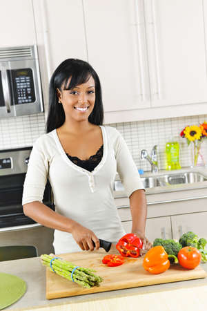 chopping board: Smiling black woman cutting vegetables in modern kitchen interior
