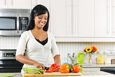 mujeres cocinando: Sonriendo cortar vegetales de mujer negra en el interior de la cocina moderna