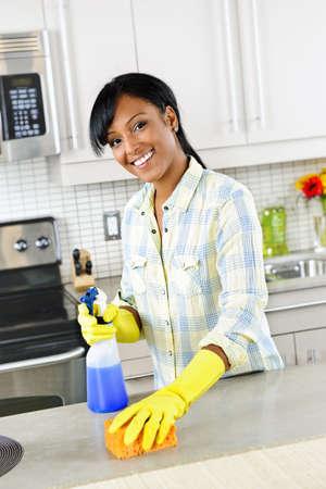 haush�lterin: L�chelnde junge schwarze Frau mit Schwamm und Gummi Handschuhe cleaning K�che Lizenzfreie Bilder