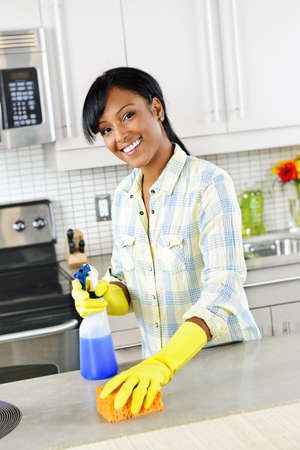 house cleaner: Smiling young black woman with sponge and rubber gloves cleaning kitchen