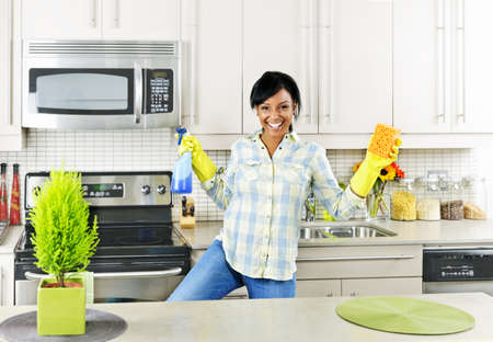 Smiling young black woman dancing and enjoying cleaning kitchen photo