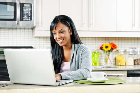 Smiling black woman using computer in modern kitchen interior Banco de Imagens