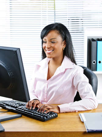 pc: Portrait of young smiling black business woman at desk typing on computer Stock Photo
