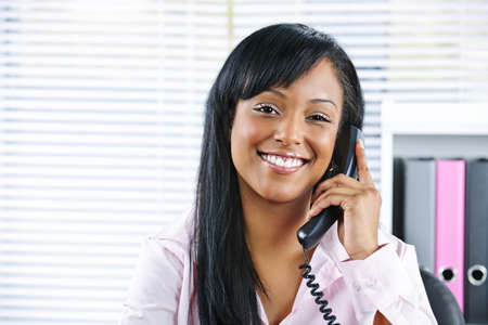 important phone call: Portrait of smiling black business woman on phone in office Stock Photo