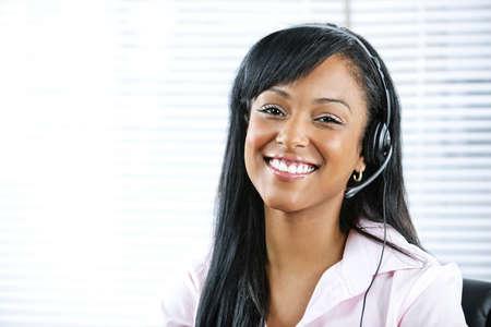 answering phone: Sonriente a mujer de servicio y soporte de cliente negro con auriculares