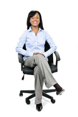 businesslike: Young smiling black businesswoman sitting in leather office chair Stock Photo