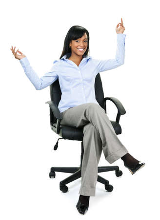 Young excited black businesswoman sitting in leather office chair