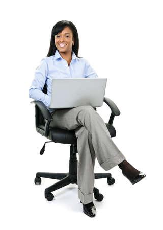 노트북 컴퓨터와 가죽 사무실 의자에 앉아 웃는 젊은 흑인 비즈니스 여자 스톡 콘텐츠