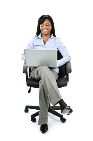 crossed legs: Young smiling black business woman sitting in leather office chair with laptop computer