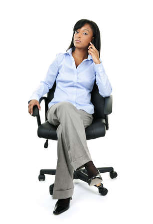 Young confident black businesswoman on phone sitting in leather office chair photo