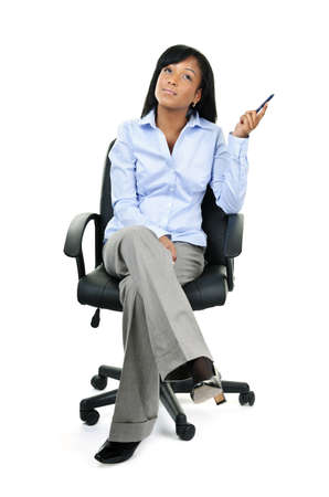 sitting on: Young black businesswoman sitting and thinking in leather office chair