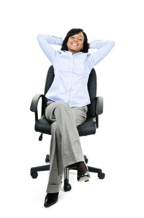 donna seduta sedia: Giovane imprenditrice nera sorridente rilassante seduta nella sedia da ufficio in pelle