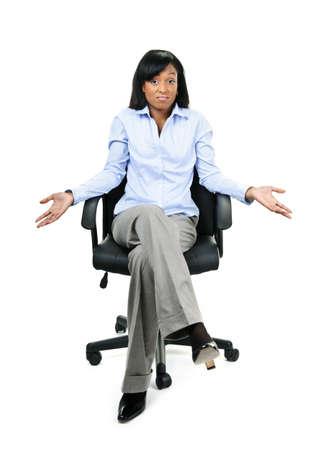 Jonge schouderophalend verward zwarte zakenvrouw in lederen stoel van het bureau zitten Stockfoto - 8967283