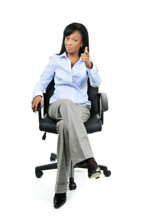 smirking: Young confident black businesswoman sitting and pointing at camera