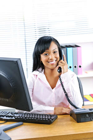Smiling young black business woman on phone at desk in office Stok Fotoğraf