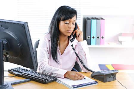 recepcionista: Mujer negra joven serio en tel�fono tomando notas en la Oficina Foto de archivo
