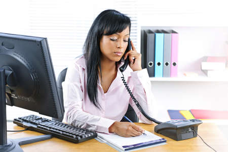 calling on phone: Serious young black business woman on phone taking notes in office