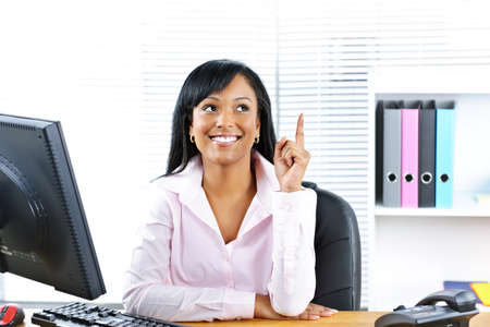 african business: Smiling black business woman pointing up with idea at desk in office