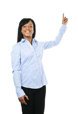dedo se�alando: Sonriente a mujer negra hacia arriba aislado sobre fondo blanco Foto de archivo